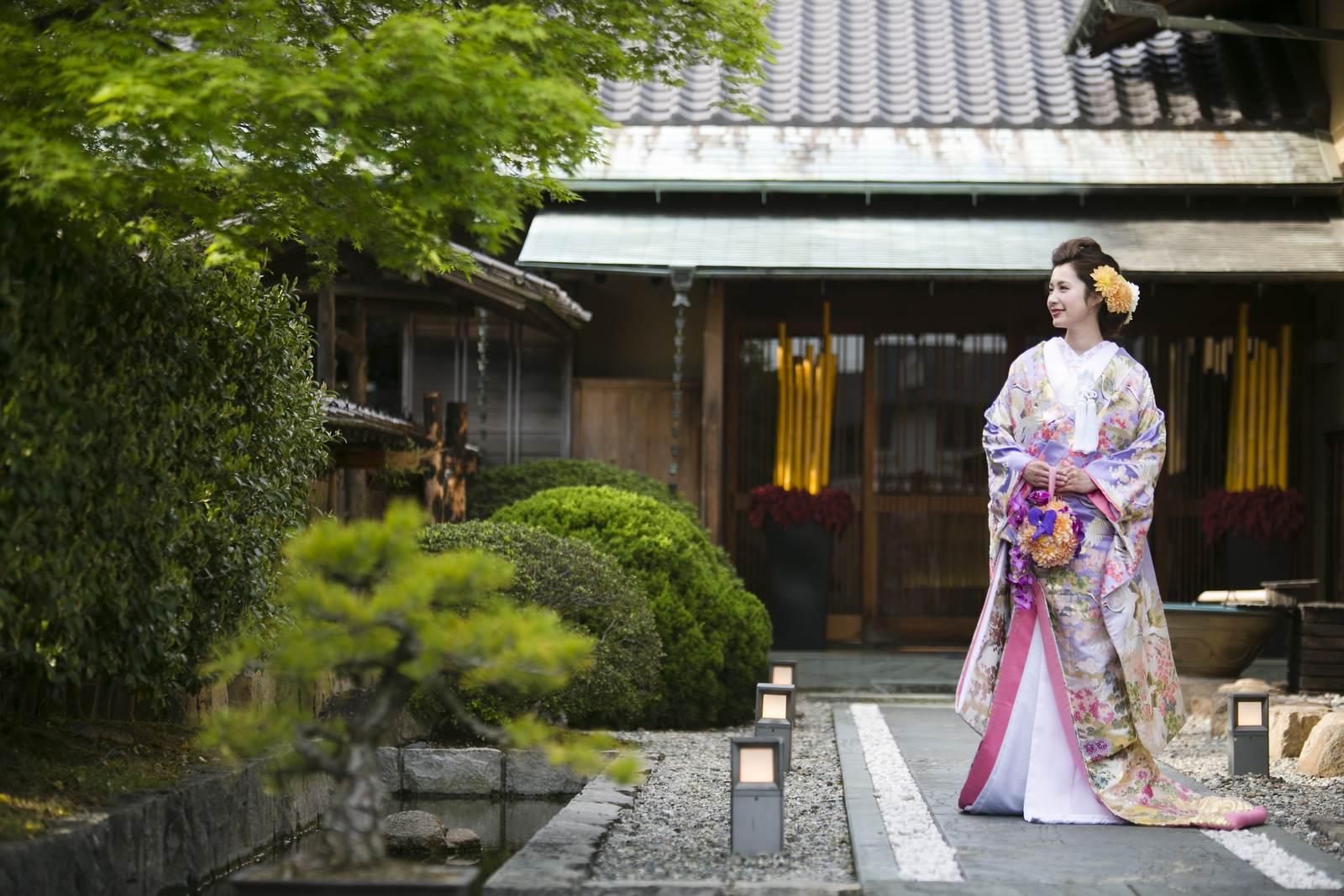 弓絃葉のアプローチで日本庭園を眺める花嫁